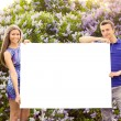 Young couple holding blank poster — Stockfoto