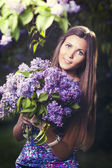 Fashion young woman with lilac flowers — Stock Photo