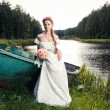 Beautiful young bride sitting on boat — Stock Photo