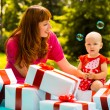 Joyful kid girl and mother with gift boxes — Stock Photo