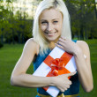 Stock Photo: Beautiful blond girl holding box with gift