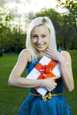 Beautiful blond girl holding box with a gift — Stock Photo