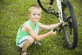 Young boy pumping thу bicycle tube — Stock Photo