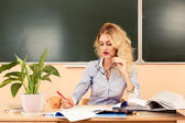 Young pretty teacher checking the tests. — Stock Photo