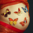 Stomach of the pregnant woman and multi-colored butterflies - Stock Photo