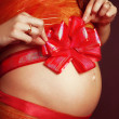 Royalty-Free Stock Photo: Pregnant girl with a red bow on her stomach