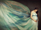 Beautiful pregnant woman in waving fabric — Stock Photo