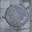 A metal sewer hatch is on the stone block pavement. — Stock Photo