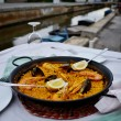 Seafood paella with glass of wine in seaside cafe,Spain — Stock Photo
