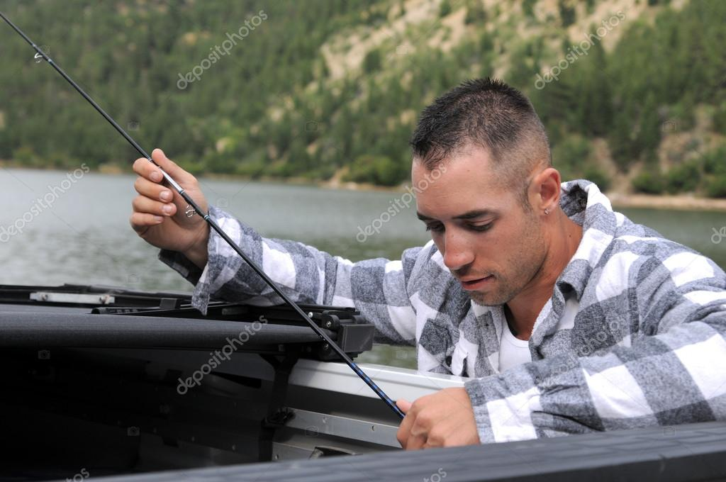 A fisherman getting his pole out of the back of his truck — Stock Photo #12105351
