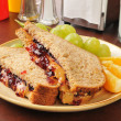 Peanut butter and jelly sandwich with fruit - Stock Photo