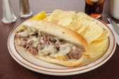 Philly cheese steak sandwich with chips — Stock Photo