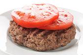 Hamburger patty with sliced tomato — Stock Photo