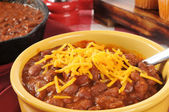 Bowl of chili with cheddar cheese — Stock Photo