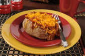 Baked potato with chili and cheese — Stock Photo