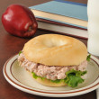 Tunafish sandwich on a bagel with schoolbooks — Stock Photo