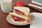 Peanut butter and jelly sandwich with school books — Stock Photo