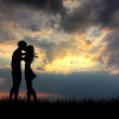 Foto Stock: Lovers kissing at sunset