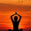 Stock Photo: Silhouette of womdoing yoga