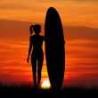 Girl surfing at sunset — Stock Photo