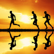 Men running at sunset — Stock Photo