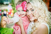 Portrait of smiling beautiful young woman and her little daughter — Stock Photo