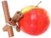 Three cinnamon sticks tied with a rope with red apple — Stock Photo