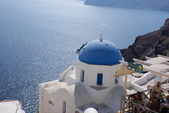 Old-style white traditional windmills in terraced village Oia of Cyclades island Santorini Greece on the blue Aegean Sea and sky background — Stock Photo