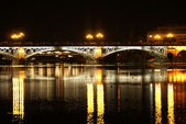 Romantic panorama of Seville riverside at down under the Triana Bridge — Stock Photo