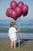 Happy child with balloons running — Stock Photo