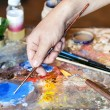 Hand of the artist with a paintbrush — Stock Photo