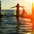 Silhouettes of jumping in ocean — ストック写真