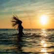 Silhouettes of woman jumping in ocean — Stock Photo