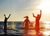 Silhouetten van springen in oceaan — Stockfoto