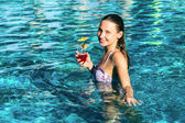 Woman with cocktail in pool — Stock Photo