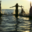 Silhouettes of jumping in ocean — Stock Photo #20798731