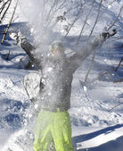 Snowboarder throwing snow in the mountains — Stock Photo