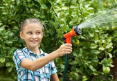 Young girl pours water from hose — Stock Photo