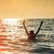 Silhouette of boy jumping in sea — Stock Photo