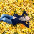 Young woman dreaming in autumn leaves — Stock Photo