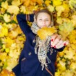 Stock Photo: Young woman dreaming in autumn leaves