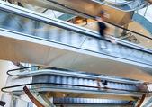 People in motion in escalators — Stock Photo