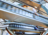 People in motion in escalators — Stock Photo