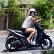 Beautiful young woman on scooter — Stock Photo
