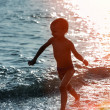 Silhouette of a boy running along the beach — Stok fotoğraf