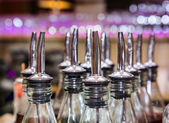 Bottles in bar with dispensers — Stock Photo