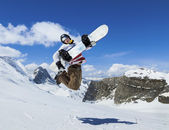 Snowboarder jumping on background of mountains — Stock Photo