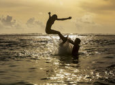 Silhouette of young woman jumping out of ocean — Stock Photo
