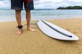 Surfer standing on sand near the ocean — Stock fotografie