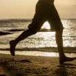 Silhouette of man running along shore of ocean — Stock Photo #44946681